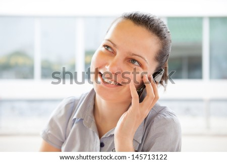 Portrait of young happy woman talking on cell phone; outdoors