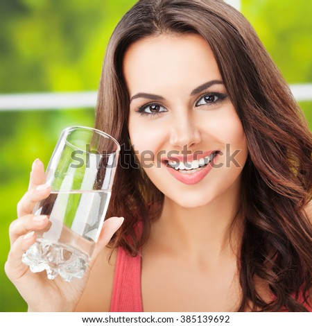 Portrait of young happy woman with glass of water - stock photo