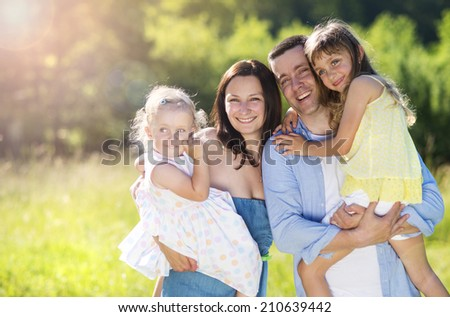 Portrait of young happy ypung family walking in sunny meadow - stock photo