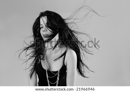 Portrait of young hispanic beauty with long dark hair in black and white
