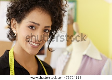 Portrait of young hispanic female dressmaker with mannequin in background. Horizontal shape, head and shoulders, copy space - stock photo