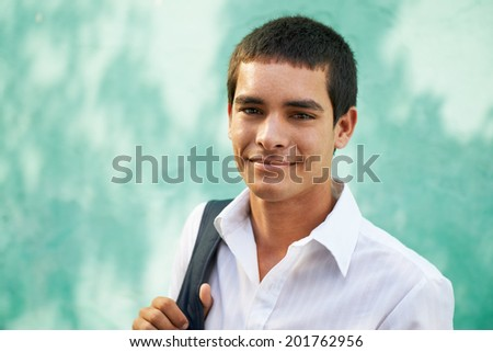 Portrait of young hispanic male student holding bag and smiling at camera smiling. Copy space - stock photo