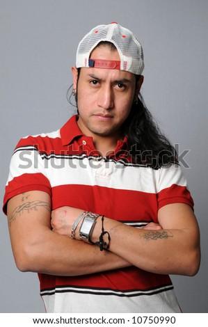 Portrait of young Hispanic man with baseball hat - stock photo
