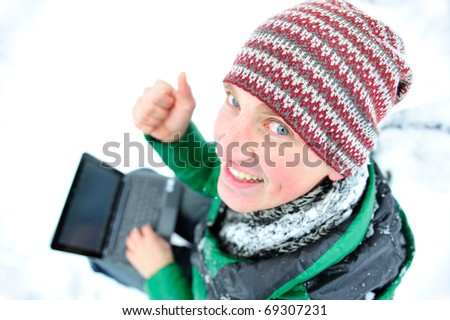 Portrait of young humorous man outdoor in winter park with his laptop enjoying wireless internet connection