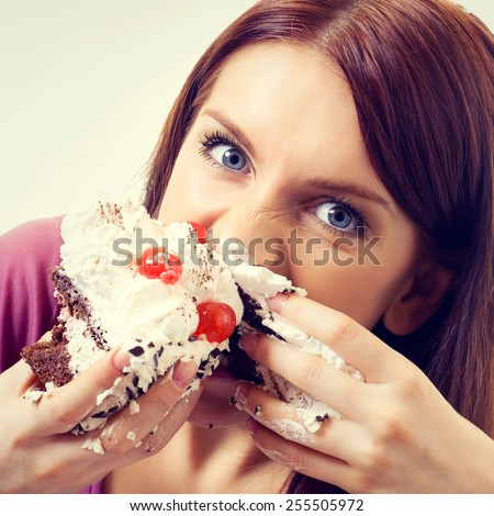 Portrait of young hungry woman eating pie - stock photo