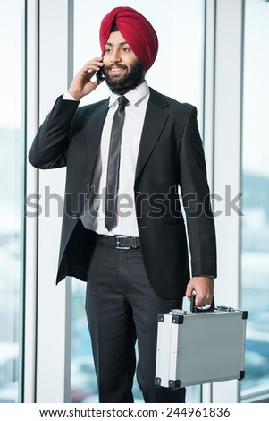 Portrait of young indian businessman with case in suit and turban. - stock photo