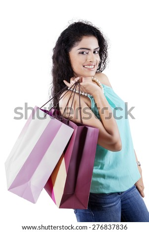 Portrait of young indian girl with curly hair smiling at the camera while holding shopping bags, isolated on white