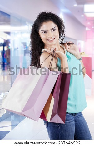 Portrait of young indian woman looking at camera while smiling and holding shopping bags in the mall - stock photo