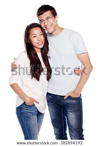 Portrait of young interracial couple, hispanic man and asian girl, wearing jeans, standing, hugging and smiling isolated on white background - relationship concept - stock photo