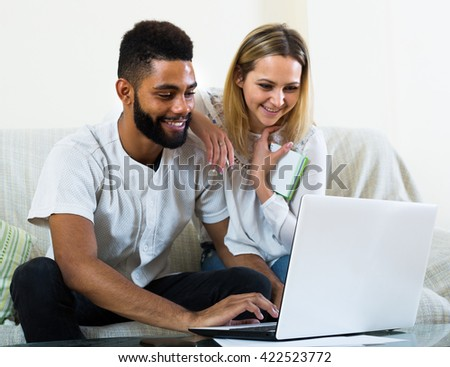 Portrait of young interracial couple with notes near laptop indoors - stock photo