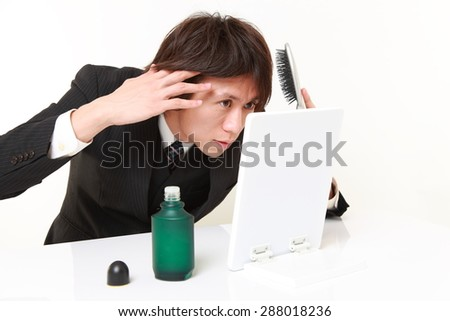 portrait of young Japanese businessman worries about losing hair - stock photo