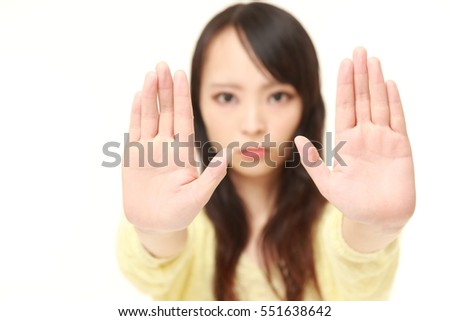 portrait of young Japanese woman making stop gesture