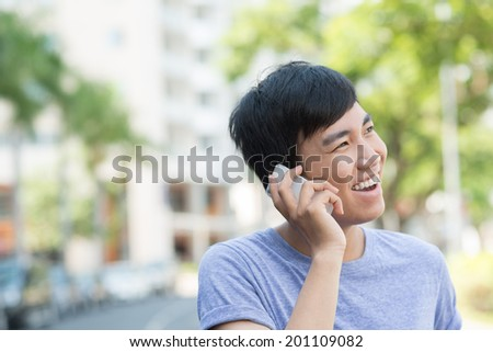 Portrait of young joyful man talking on the phone outdoors - stock photo