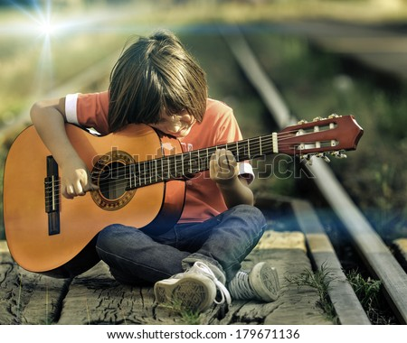 Portrait of young kid playing guitar  - stock photo