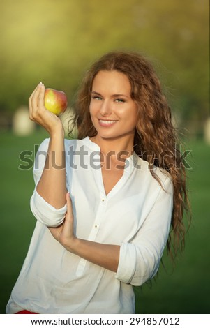 Portrait of young lady keeping apple. Girl with long red hair smiling for camera in beautiful sunset.  - stock photo