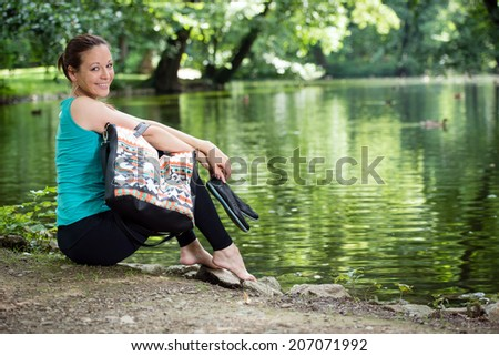Portrait of young lady with handbag sitting by the lake in a park - stock photo