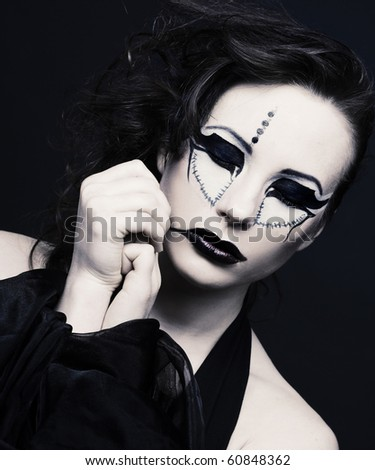 Portrait of young lady with original make-up in dark style - stock photo