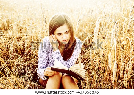 Portrait of young latin hispanic girl sitting on golden reap wheat in yellow sunset field reading black book on summer nature background. Woman with long brunette hair laugh and looking at paper page - stock photo