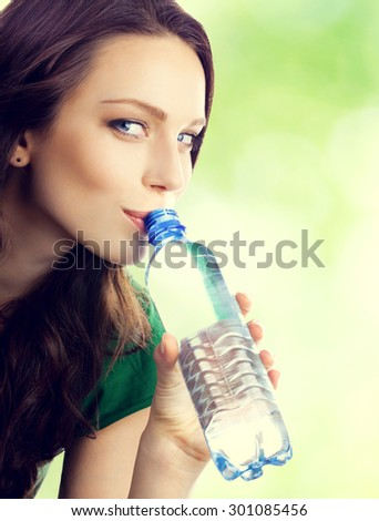 Portrait of young lovely brunette woman drinking water from bottle, outdoor - stock photo