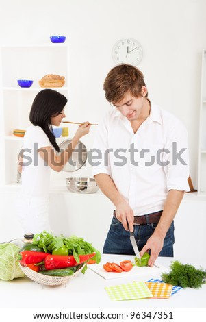 portrait of young lovely couple slicing tomato in their kitchen, happy smile - stock photo