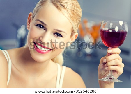 Portrait of young lovely woman with glass of red wine, at home