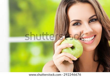 Portrait of young lovely woman with green apple, outdoors, with copyspace - stock photo