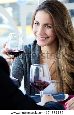 Portrait of Young loving couple celebrating with red wine at restaurant - stock photo
