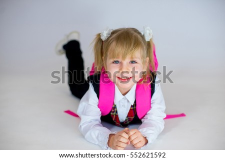 portrait of young lying schoolgirl with pink schoolbag. isolated on white background
