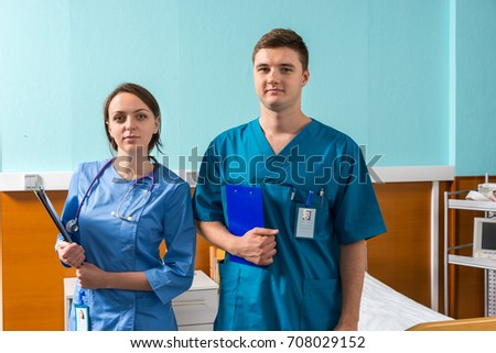 Portrait of young male and female doctor in uniform with phonendoscope on her neck holding clipboards while standing in the hospital ward. Healthcare concept