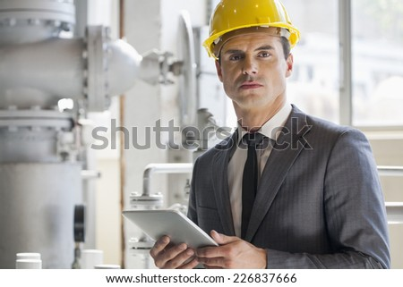 Portrait of young male architect holding tablet computer in industry - stock photo