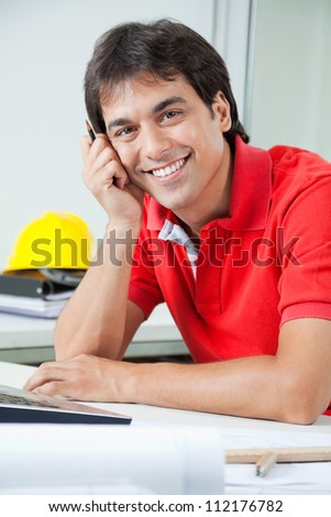 Portrait of young male architect smiling while sitting by desk with laptop - stock photo
