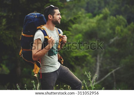 Portrait of young male backpacker with a rucksack standing on the mountain hill while enjoying nature scenery view with plants copy space area background for your text message or advertising content  - stock photo