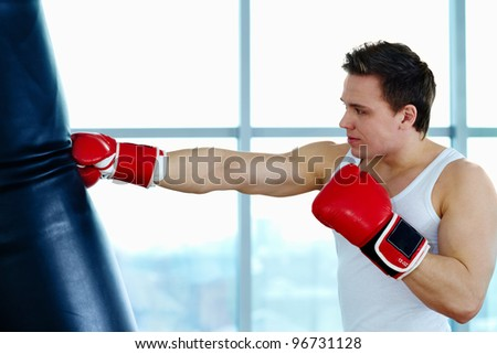 Portrait of young male boxer training in gym