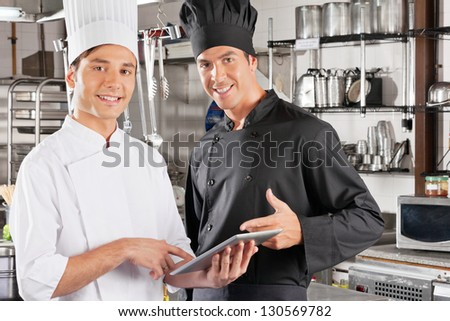 Portrait of young male chefs holding digital tablet in commercial kitchen