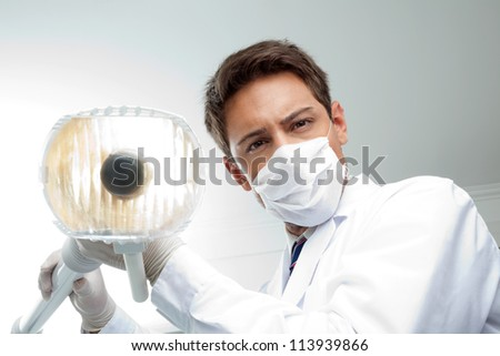 Portrait of young male dentist wearing surgical mask while holding dental lamp - stock photo
