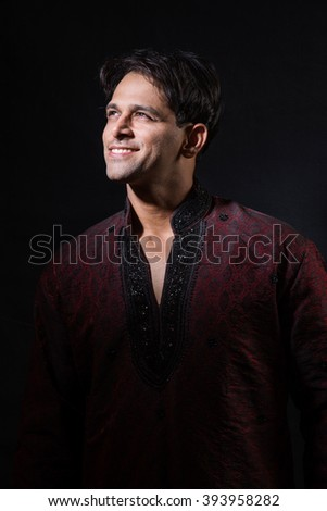 portrait of young male indian model, isolated over black background highlighting face, indian model posing in ethnic clothing - stock photo