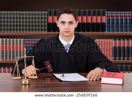 Portrait Of Young Male Judge Striking Gavel In Courtroom - stock photo