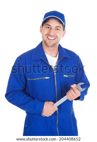 Portrait of young male mechanic in blue overalls holding spanner over white
