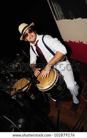 Portrait of young male percussionist playing cuban drums against black background - stock photo