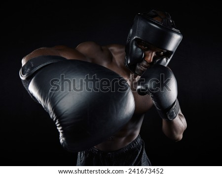 Portrait of young male practicing boxing against black background. African Male boxer throwing a punch in front. Young sportsman training boxing. - stock photo