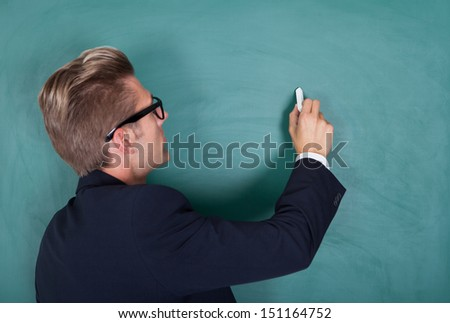 Portrait Of Young Male Professor Writing On Chalkboard In Classroom - stock photo