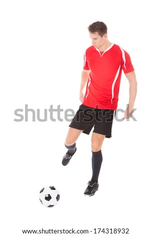 Portrait Of Young Male Soccer Player Kicking Football - stock photo