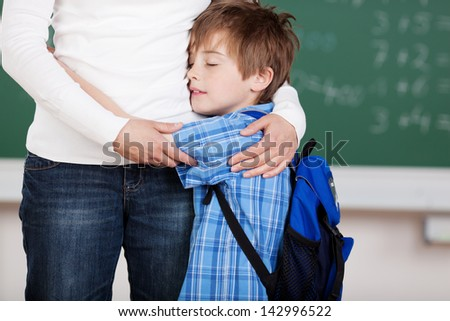 Portrait of young male student embraced his mother after school - stock photo