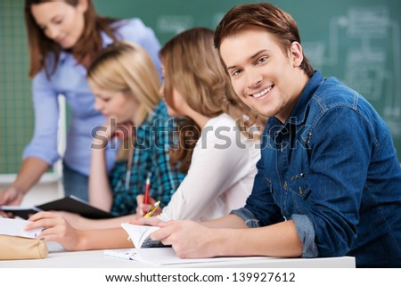 Portrait of young male student holding book while sitting with female classmates and teacher at desk - stock photo