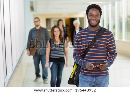 Portrait of young male student holding digital tablet while standing on university corridor - stock photo