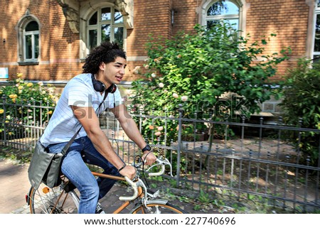 portrait of young male student with a bicycle in the town - stock photo
