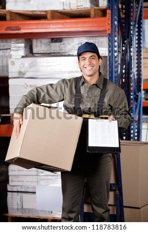 Portrait of young male supervisor holding clipboard and cardboard box at warehouse