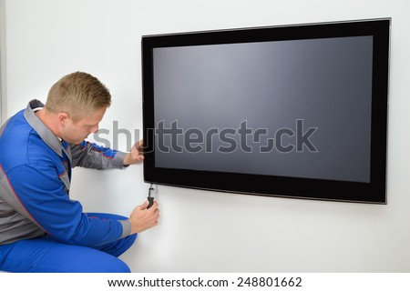 Portrait Of Young Male Technician Repairing Television - stock photo