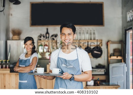 portrait of young male waiter serving coffee at his own cafe