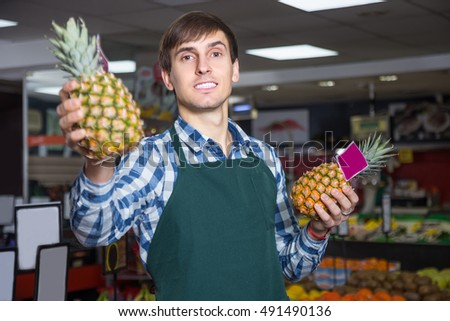 Portrait of young male working in grocery and smiling